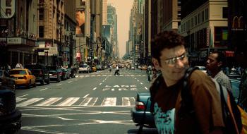 Ihmisiä ja autoja suurkaupungin kadulla, taustalla pilvenpiirtäjiä