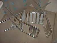 Kaksi alumiinista, lumista puutarhatuolia kylpyhuoneen lattialla kumollaan