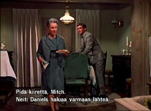 """Lydia ja Mitch kattavat pöytää. Lydia sanoo: """"Neiti Daniels haluaa varmaan lähteä."""""""
