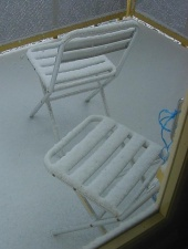 Kaksi lumista parvekkeen tuolia