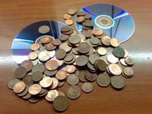 Läjä pieniä eurokolikoita kahden optisen levyn päällä