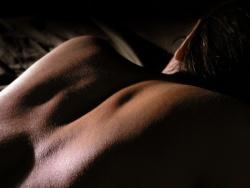 Mahallaan makaavan ihmisen paljas yläselkä hämyisässä valaistuksessa.