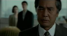 Johtaja Shindo, taustalla Terasawa kustannustoimittajansa kanssa