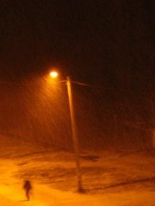 Ihminen suurpainenatriumlampun valokeilassa, lumisateessa