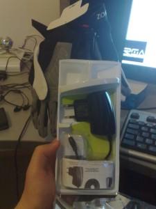 Cellular Line -laturi pakkauksessaan, taustalla pyöräilyhanskat (ja kuulokkeet, Kotiboksi, webkamera, näppäimistö, näyttö jossa RSAudion logo)