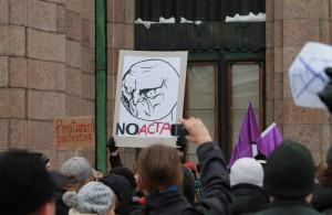 """Kylttejä Stop ACTA -mielenosoituksessa Helsingin rautatieaseman edustalla. """"Piratismin puolesta?"""" ja """"NO ACTA"""", taustalla Piraattipuolueen lippuja."""